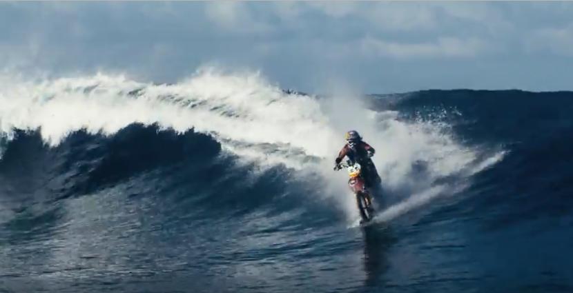 A dirt bike surfs the waves